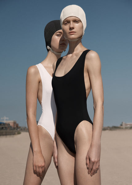 2 women standing one in a white one piece, the other in black one piece