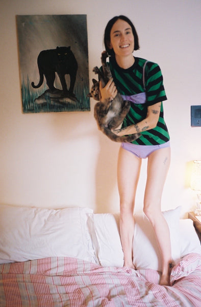 woman standing and holding cat while wearing purple panty and green and navy stripped shirt