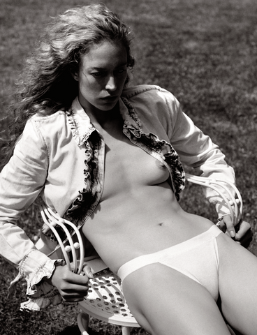 woman sitting wearing unbuttoned ruffle top and nude panty