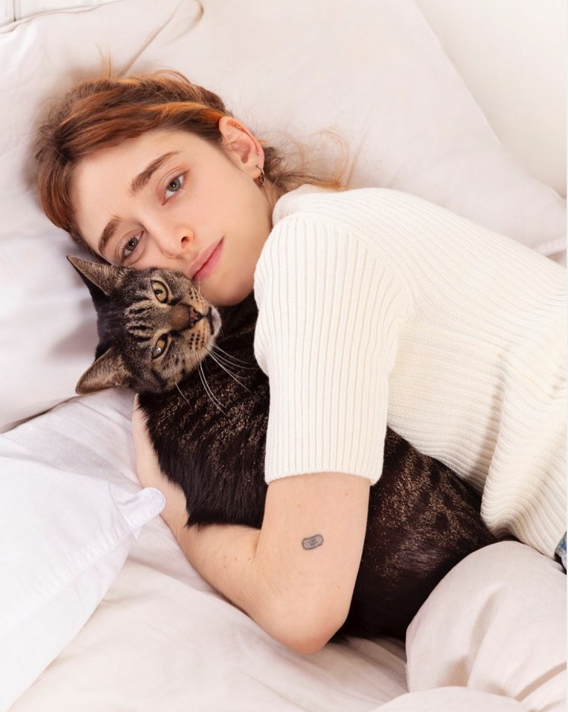 Woman in a white sweater holding onto her cat in bed.
