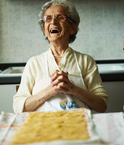 Older woman laughing with a plate of pasta.