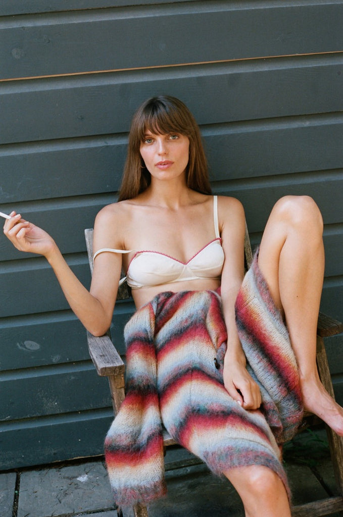 woman sitting in chair with cigarette wearing cream bra and multicolored sweater
