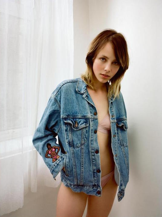 woman standing wearing matching pink bra and panty and denim jacket