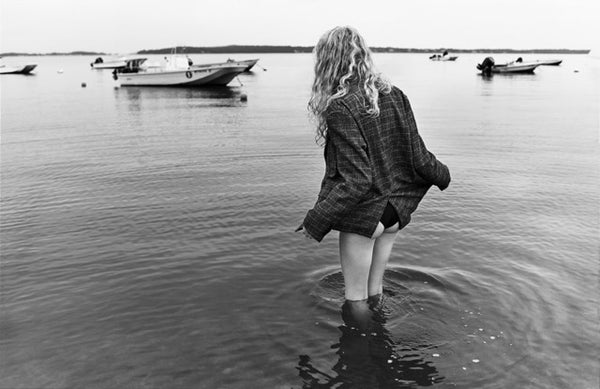 woman standing in water with flannel shirt and black bottoms