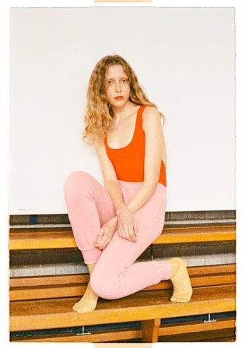 woman sitting on bench in orange top and pink pant
