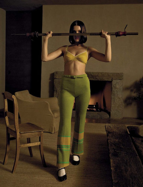 Woman standing in yellow bra and green pants