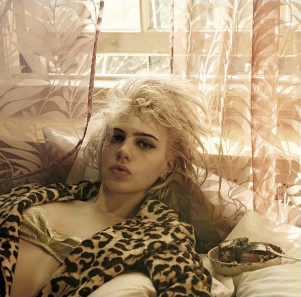 woman laying on bed wearing leopard print jacket and gold bra