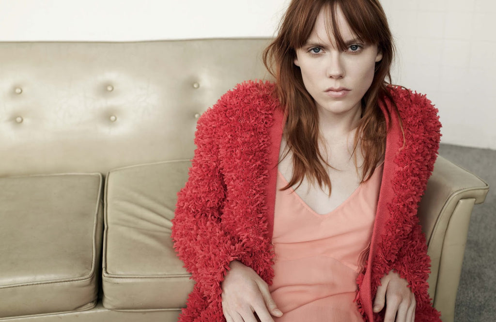woman sitting on couch in pink slip and pink jacket