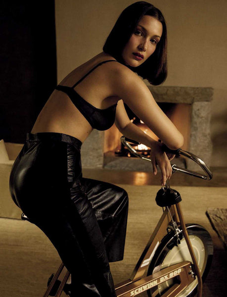 woman leaning on stationary bicycle wearing black bra and black bottom