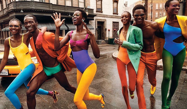 4 women and 2 men wearing bright colored swimwear and tights