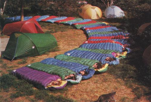 Tents surrounded by people sleeping in colorful sleeping bags.
