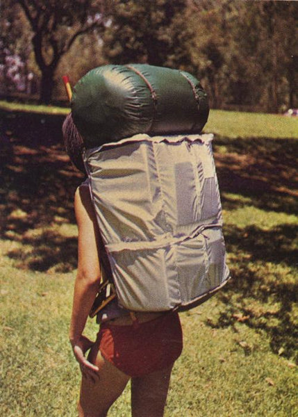 Back view of a woman carrying large back pack and sleeping bag.