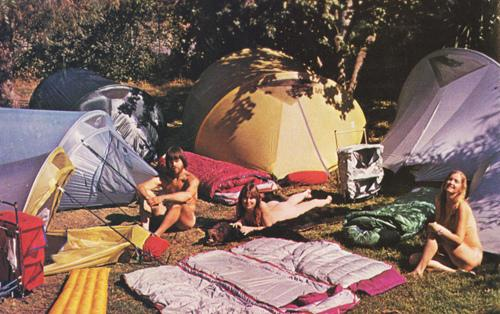 Two nude women and a nude man sitting by open sleeping bags and tents.