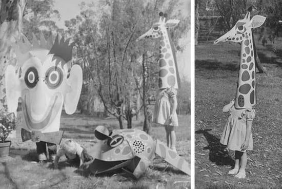 Black and white photo of a large paper monkey, frog and giraffe heads on kids.