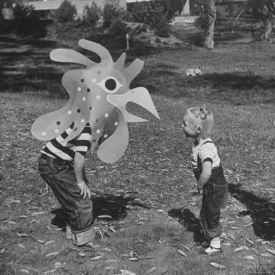 Black and white photo of a kid wearing a large paper rooster head bent over talking to another kid.