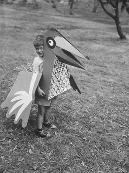 Black and white photo of a kid holding a large paper bird head.