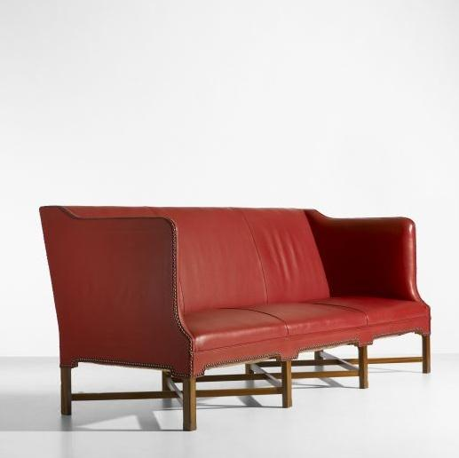 Red leather couch with brown legs.