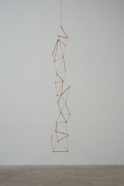 Gold chain sculpture of triangles.