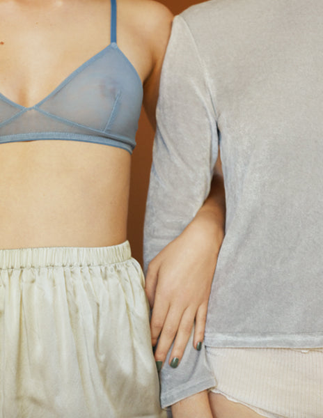 1 woman in blue bralette and cream panty, 1 woman in grey top and cream panty