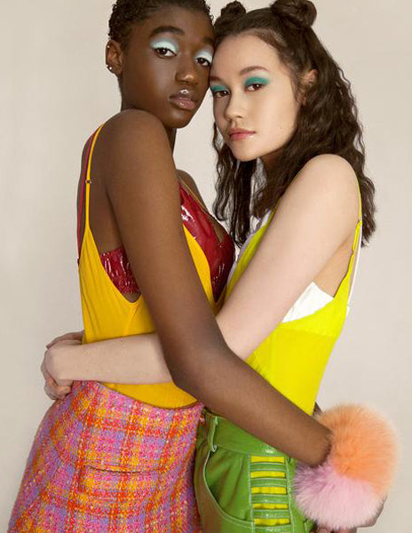 women hugging in yellow one pieces and skirts