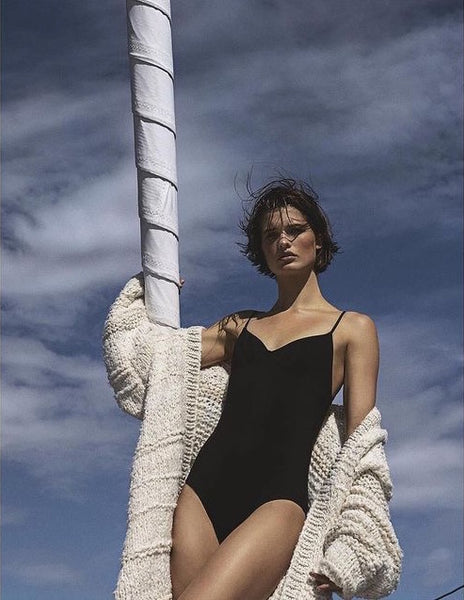 Woman standing next to pole in black one piece and white sweater