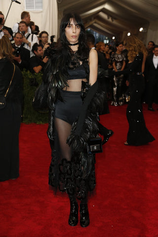 woman standing on red carpet in black feathered jacket and matching black bralette and high waisted panty