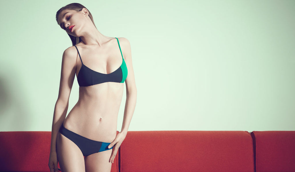 Woman wearing an asymmetrical color-blocked navy and green bikini top with slight v neckline with matching color-blocked navy and blue low-rise bikini bottom.