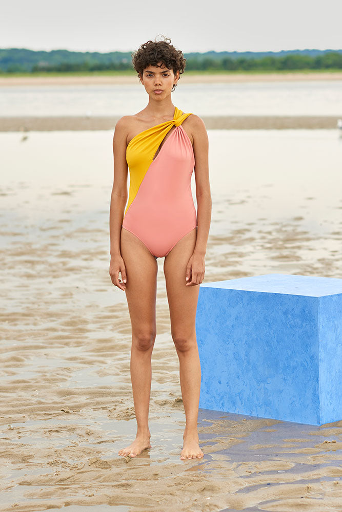 Woman wearing a yellow and peach asymmetrical one piece swimsuit with a split neckline and doubled one shoulder strap.