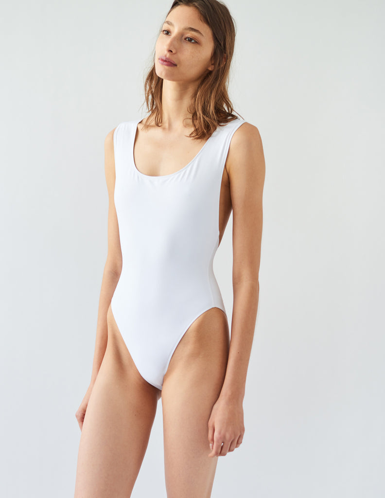 Woman wearing white one piece swimsuit with wide shoulder straps that intersect at back.