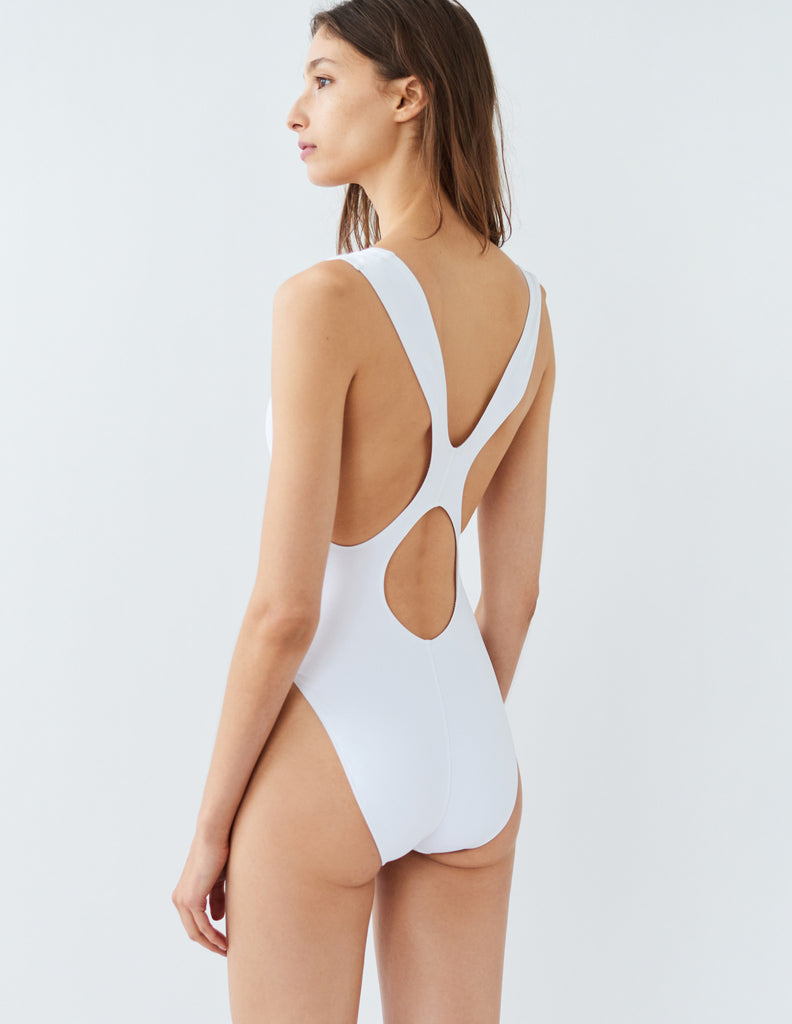 Back shot of woman wearing white one piece swimsuit with wide shoulder straps that intersect at back.