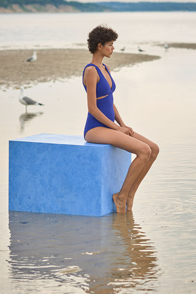 Woman wearing a blue ribbed one piece swimsuit with a deep v neckline and side slits.