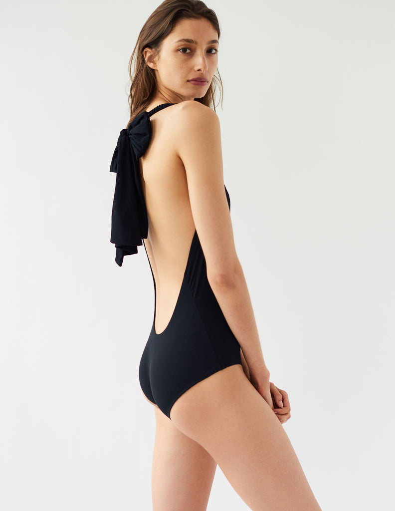 Woman facing sideways, in black swimsuit