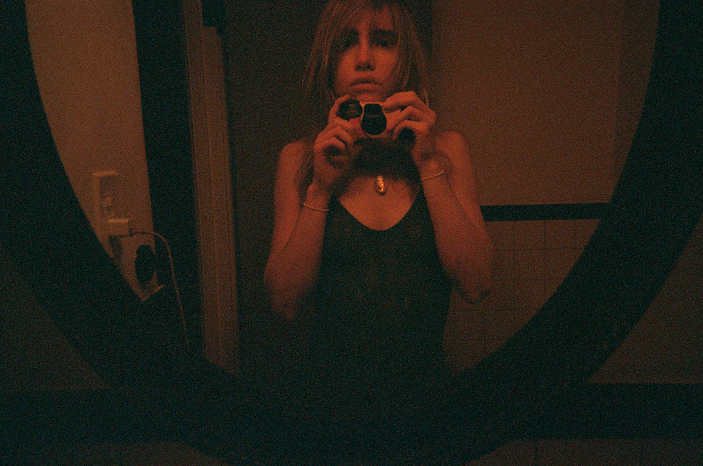 Woman taking a photo of herself in a mirror in a black body suit.