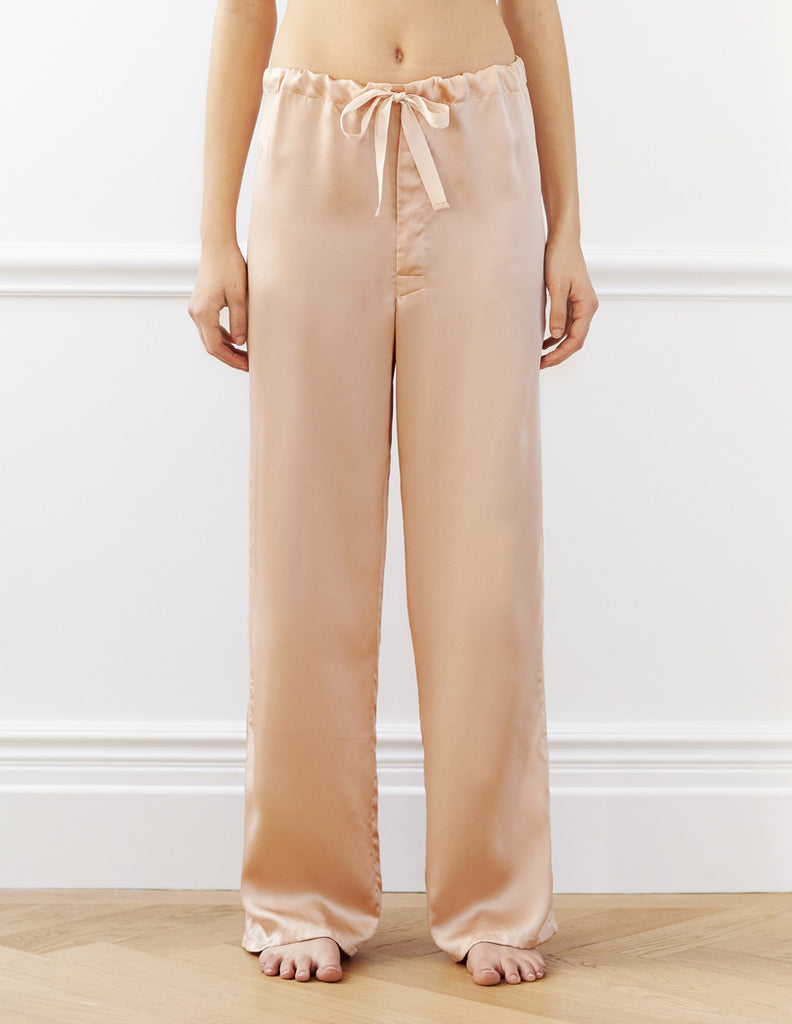 Woman wearing nude silk pajama pants with a cotton twill tape drawstring.