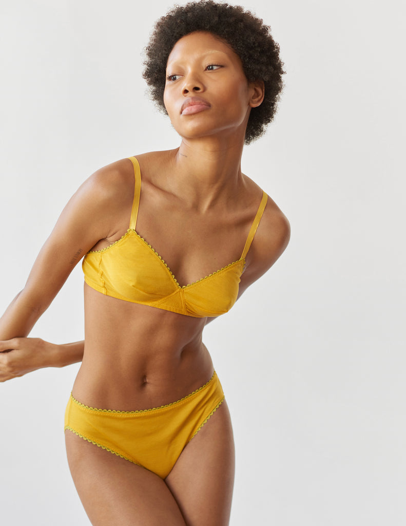 A woman wearing a yellow cotton Antonia Bralette and cotton Isabella panty.
