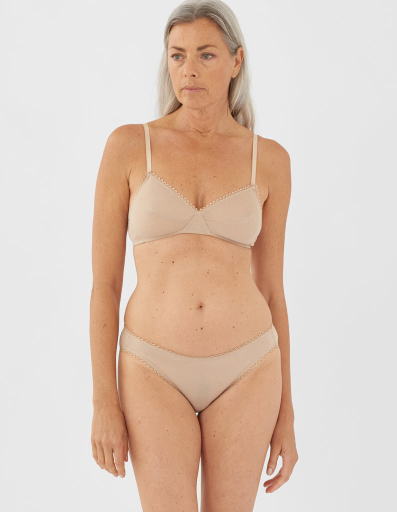 Front view of woman wearing nude panty with nude trim, and matching bralette.