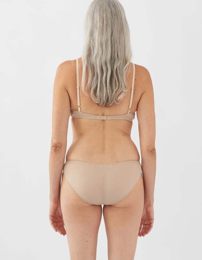 Back view of a woman wearing nude bralette with nude trim and matching panty.