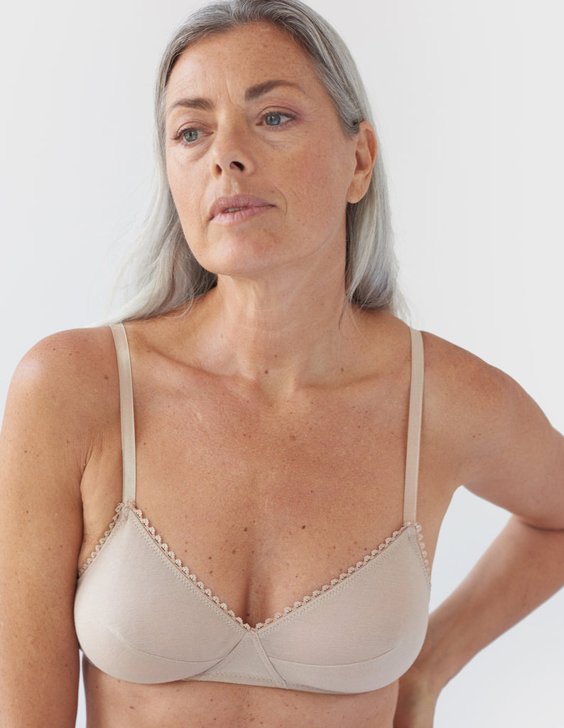 Front view of a woman wearing nude bralette with nude trim.