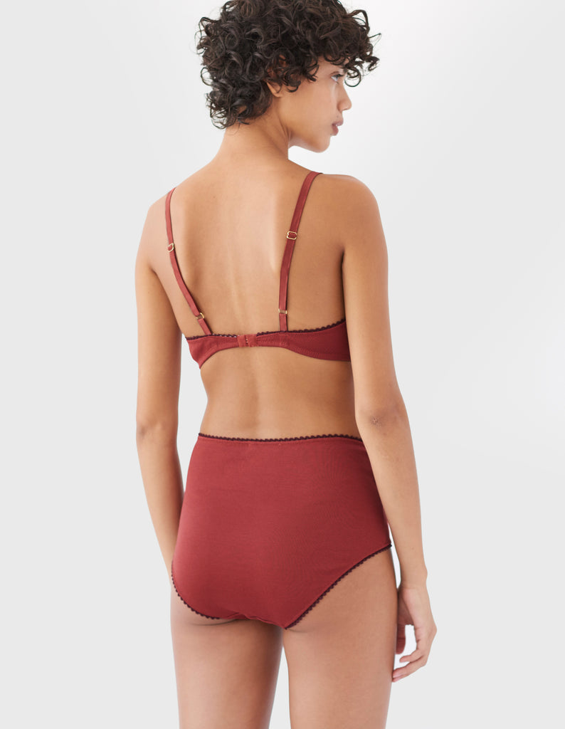 back of woman wearing red cotton wireless bralette with brown trim and matching high waist panty