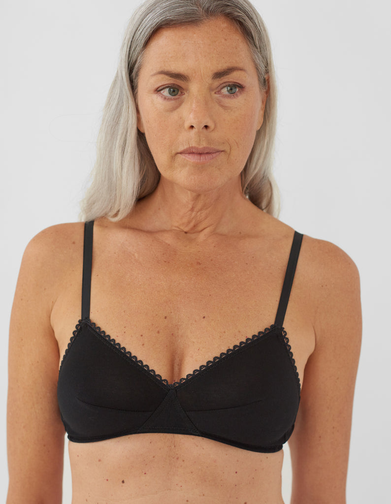 Front view of woman wearing black bralette with black trim