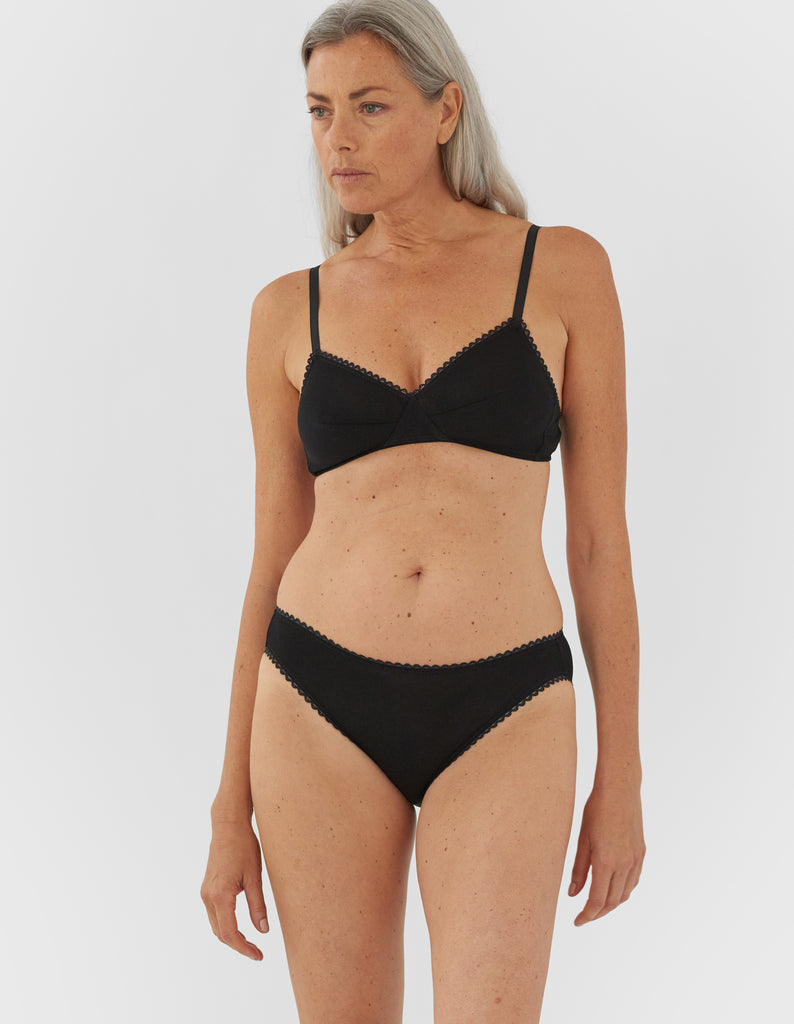 Front view of woman wearing black bralette with black trim and matching panty.