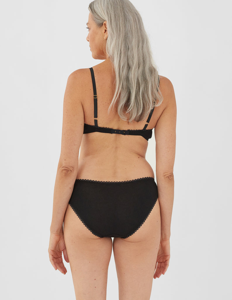 Back view of woman wearing black panty with white trim, and matching bralette.