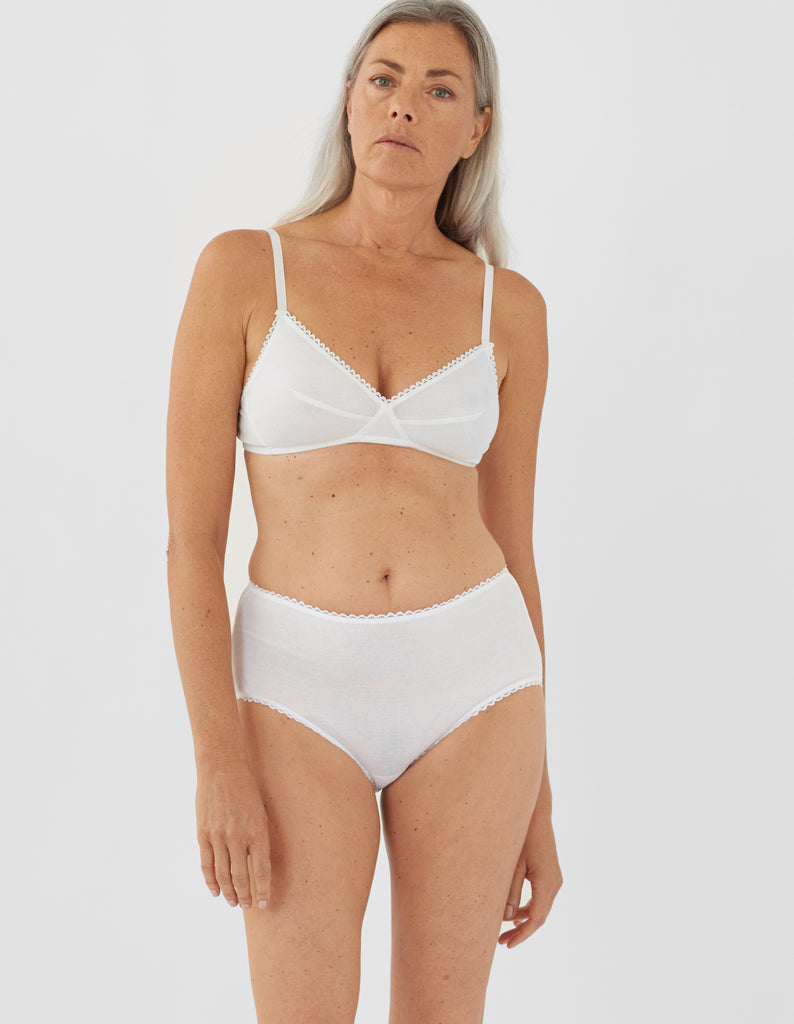 Woman wearing white high-waist cotton panty with white scallop trim on waist and leg openings with matching bralette.