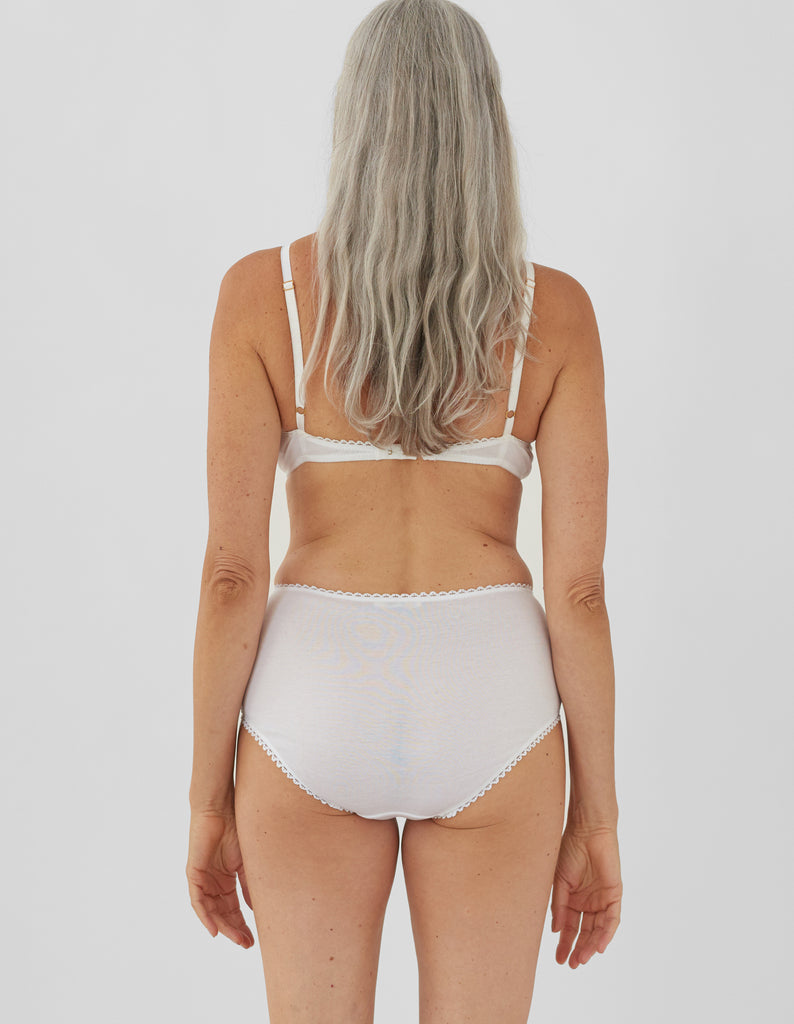 Back shot of woman wearing white high-waist cotton panty with white scallop trim on waist and leg openings with matching bralette.