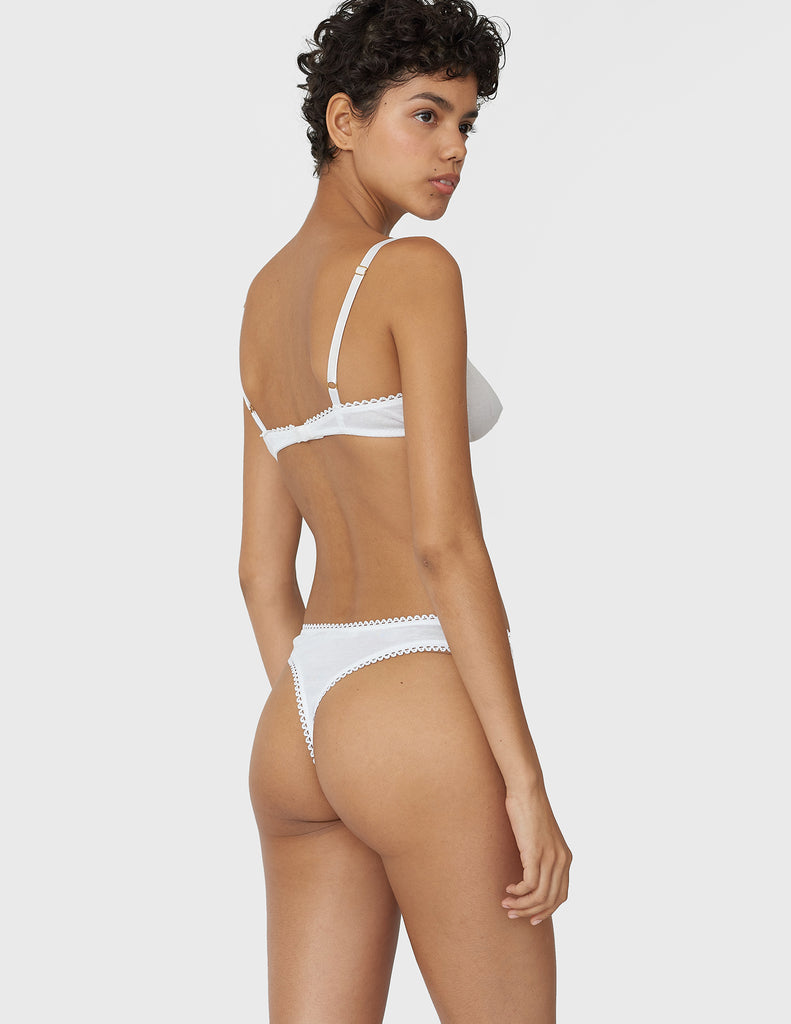 Back view of woman wearing white cotton thong with white trim and matching bra.
