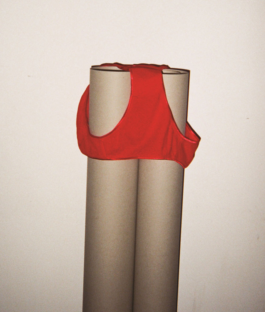 Red mid-rise panty draped on top of two rolls of paper.