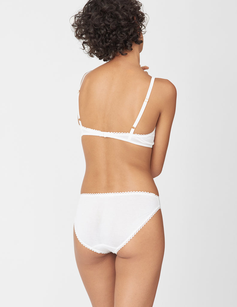 Back view of woman wearing white panty with white trim, and matching bralette.