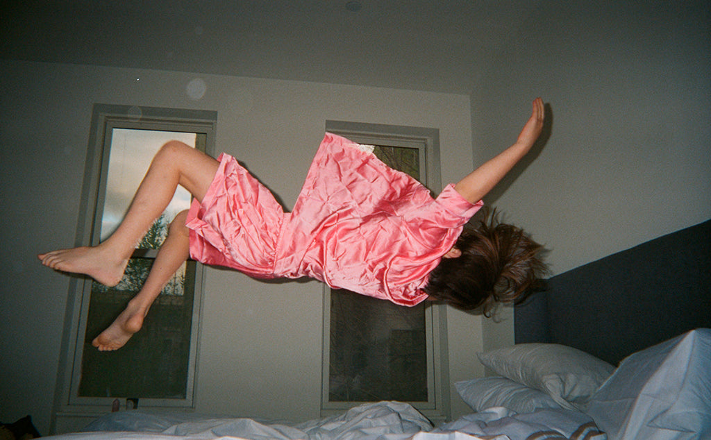 Woman jumping on a bed wearing pink silk collared short-sleeved sleep shirt with left breast pocket and contrast piping and matching shorts.
