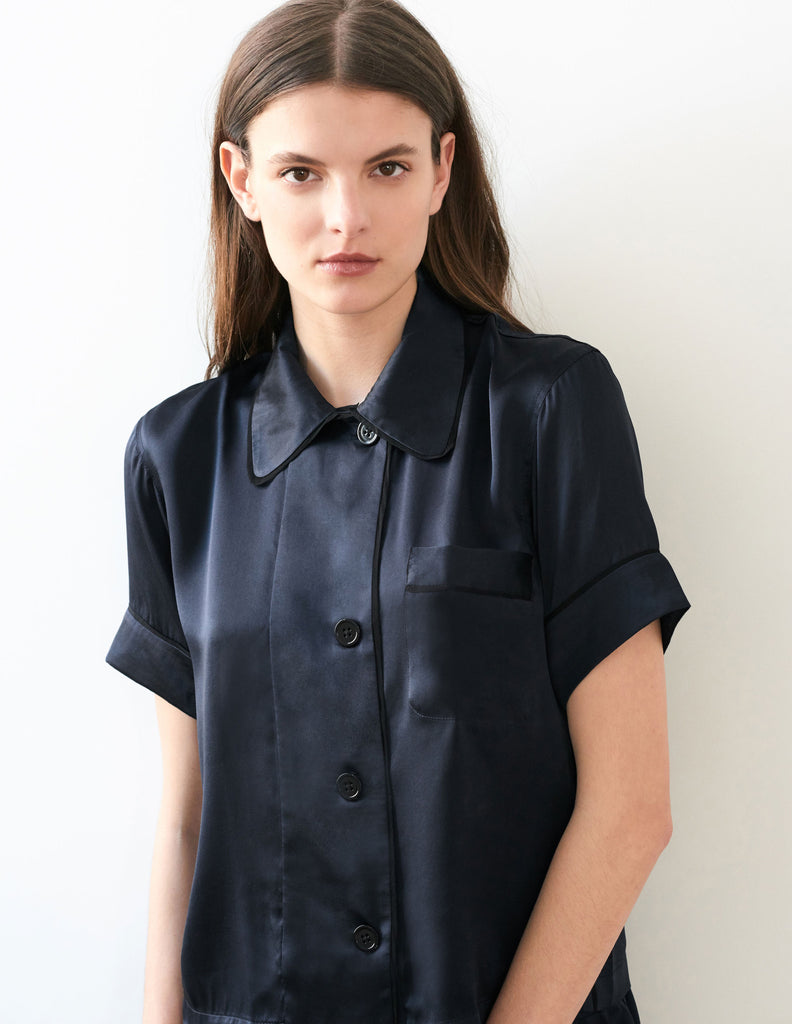 Close up, woman wearing navy silk collared short-sleeved sleep shirt with left breast pocket and contrast piping