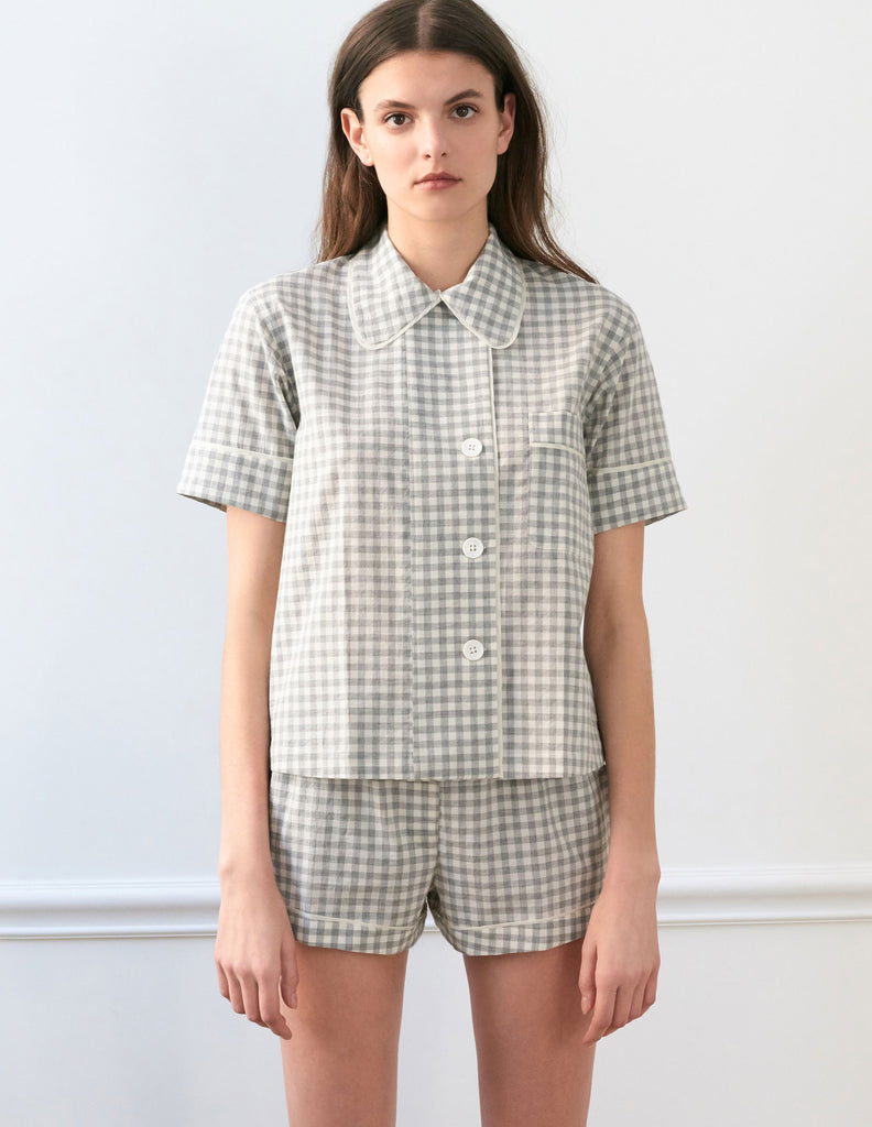 Woman wearing light grey cotton collared short-sleeved sleep shirt with left breast pocket and contrast piping and matching shorts